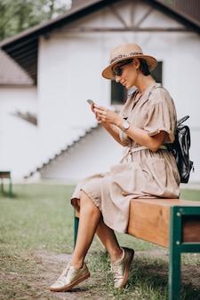 電話を使用して公園に座っている若い女性