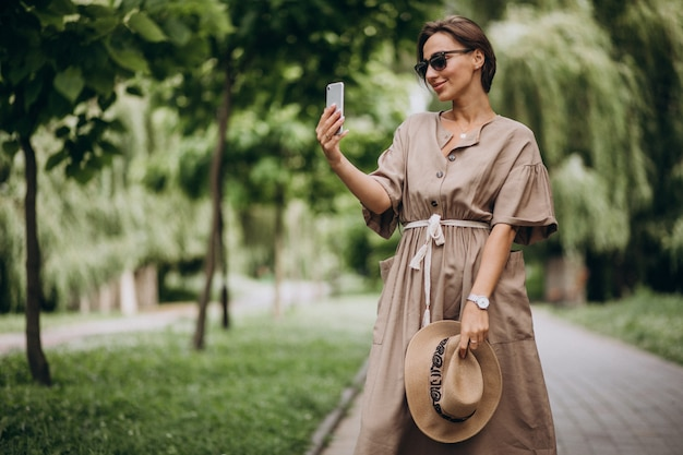 Молодая женщина с мобильным телефоном в парке