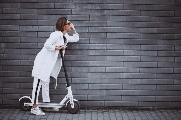 白い乗馬スクーターに身を包んだ若い女性