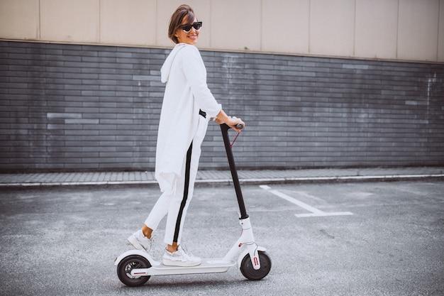 Молодая женщина в белом скутере