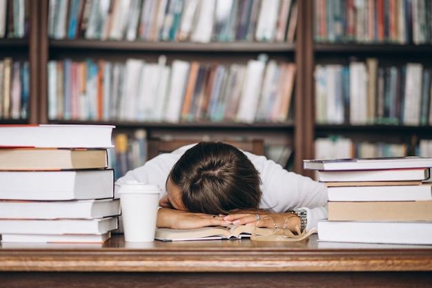 テーブルの上の図書館で寝ている学生