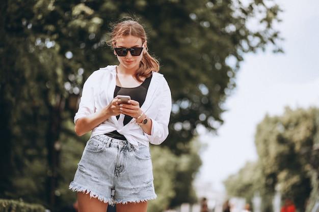 電話を使用して通りの外のきれいな女性