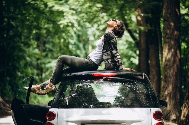 森の中の車の屋根に座っている女性