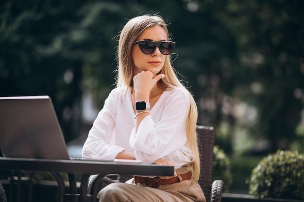 Молодая бизнес-леди работая на компьтер-книжке снаружи в кафе