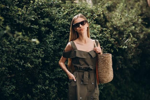 Молодая женщина, стоящая в парке на фоне зеленого куста