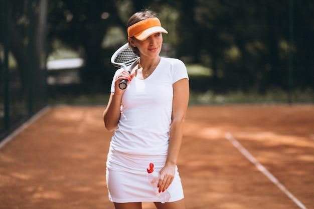Молодая женщина играет в теннис и питьевой воды в суде