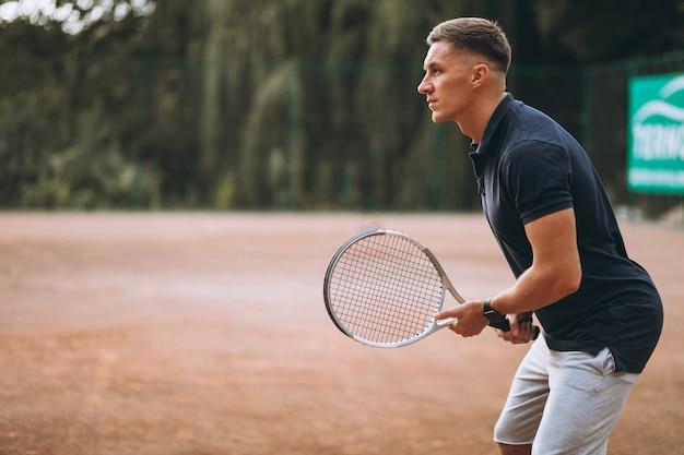 Молодой человек играет в теннис на корте