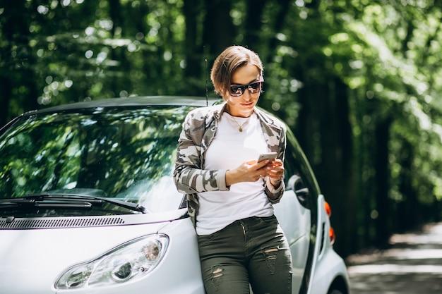 Женщина, стоя у машины в парке с помощью телефона