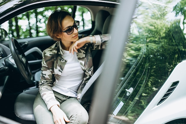 Женщина сидит в машине в лесу
