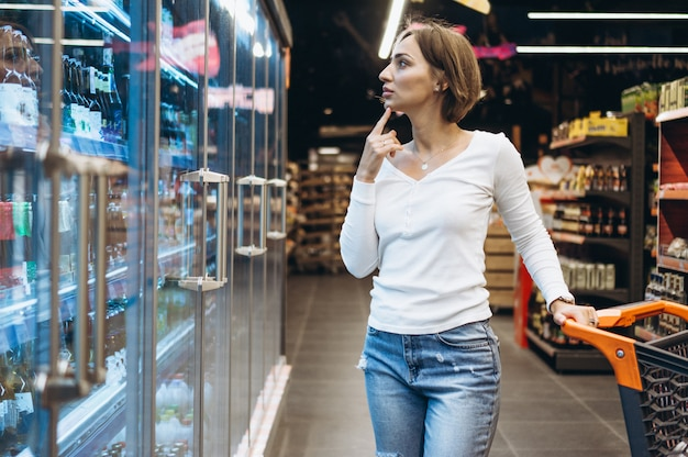 Женщина за покупками в продуктовом магазине, у холодильника