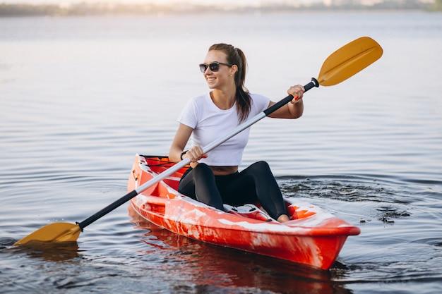 若い女性が湖でカヤック