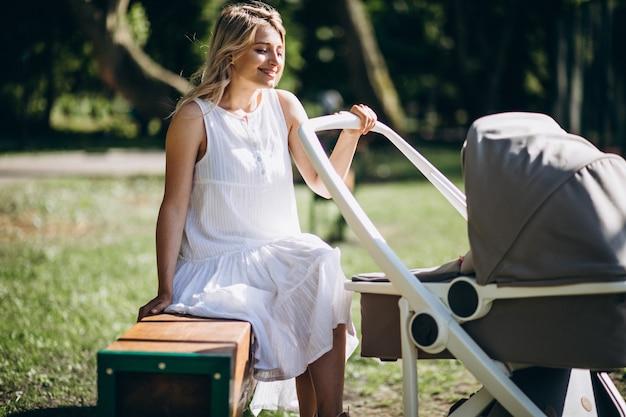 公園のベンチに座っている小さな赤ん坊の娘を持つ母