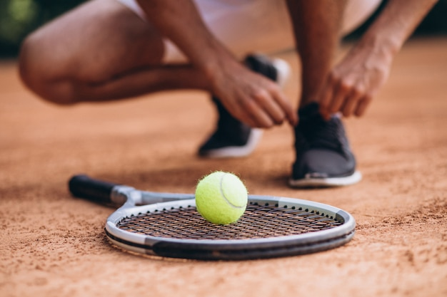 Молодой человек теннисист на корте, теннисная ракетка крупным планом