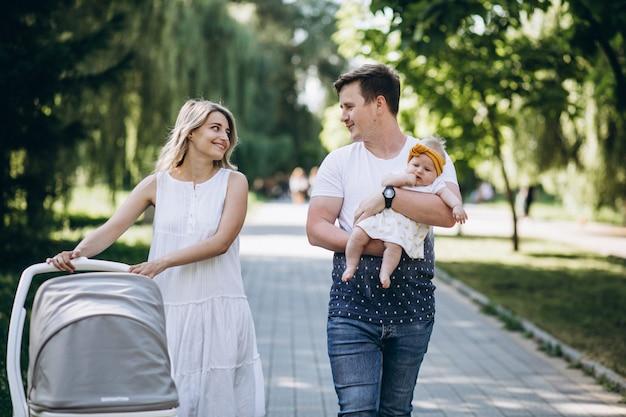 公園で彼らの赤ん坊の娘と若いカップル