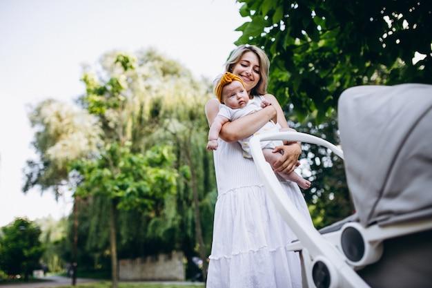 公園を歩いて小さな赤ん坊の娘を持つ母
