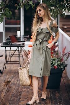 カフェの外の夏の服装の若い女性