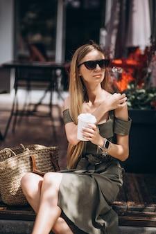 カフェの外でコーヒーを飲む若い女性
