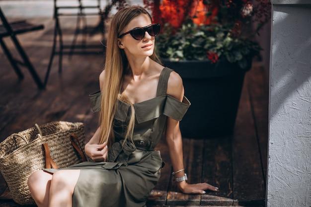 Молодая женщина, сидя за пределами кафе
