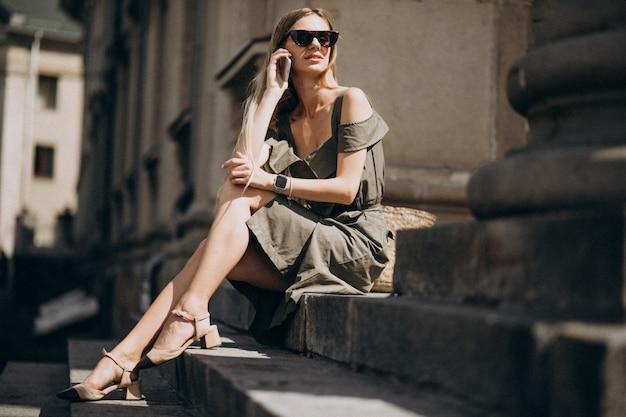 Молодая женщина сидит на лестнице и разговаривает по телефону