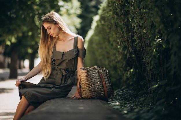 公園に座っている緑のドレスの若い女性