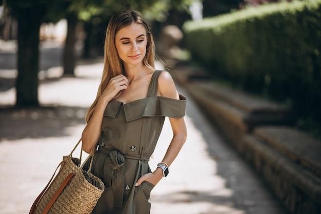 公園の外の緑のドレスの若い女性