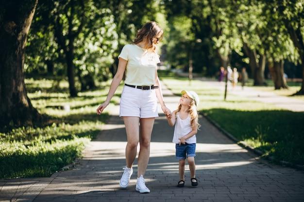 Молодая женщина с маленькой дочерью гуляя в парк