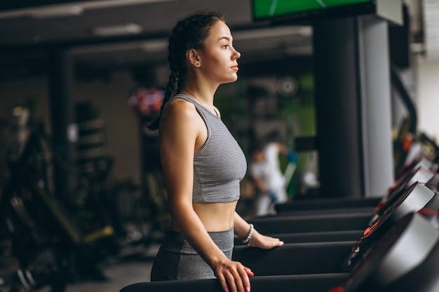 Женщина на беговой дорожке в тренажерном зале