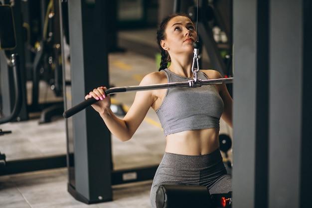 Женщина занимается в тренажерном зале сама