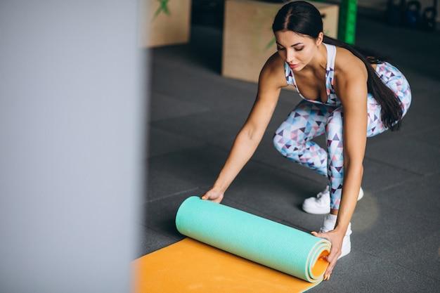 ヨガのマットを保持しているジムで運動する女性