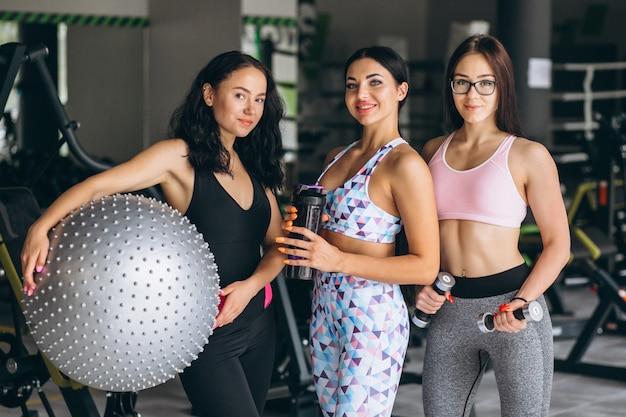 Три молодые женщины тренируются в спортзале