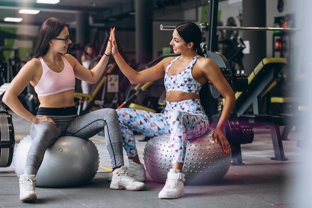 Две молодые девушки тренируются в тренажерном зале, сидя на фитнес-мяче