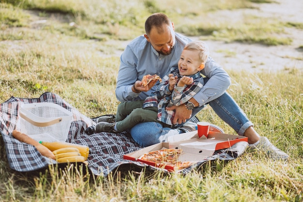 公園でピクニックを持つ息子を持つ父