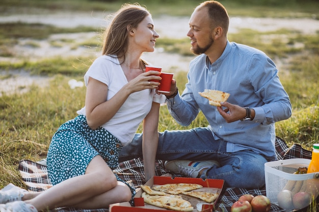 公園でピザとピクニックを持っている若いカップル