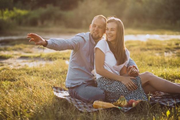 公園でピクニックを持っている若いカップル