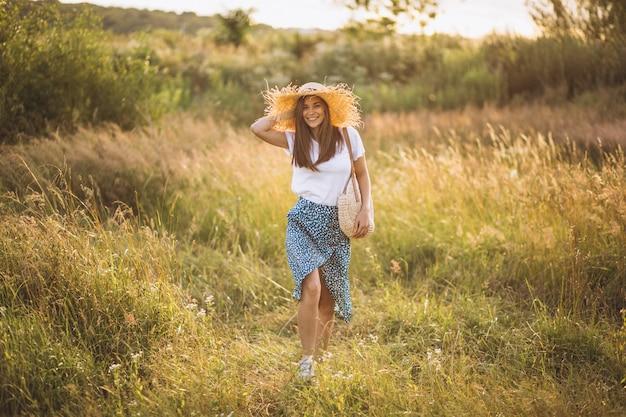 フィールドに大きな帽子のバッグで立っている若い女性