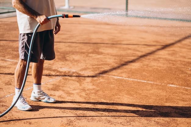 試合前にテニスコートに水をまく男