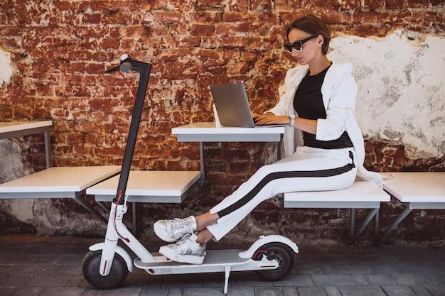 Молодая женщина работает на ноутбуке в кафе