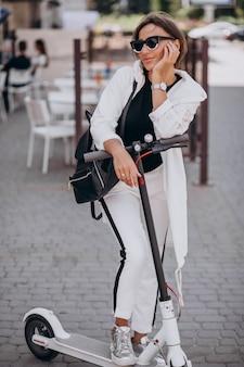 通りで若い女性乗馬スクーター