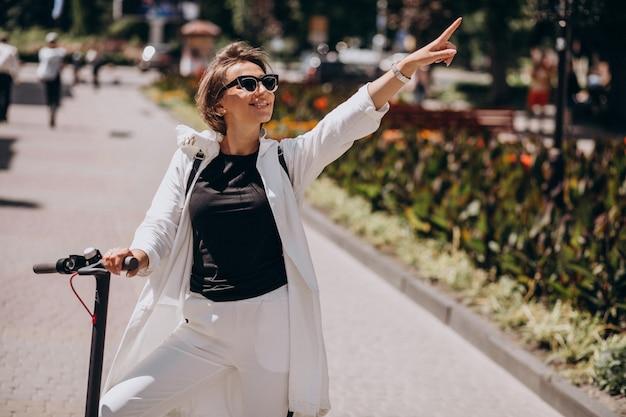 Молодая женщина верхом скутер на улице