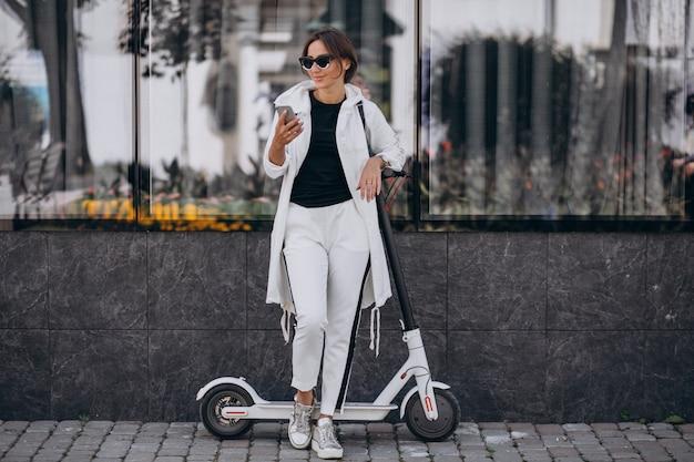 Скоттер езда молодой женщины в городе и с помощью телефона