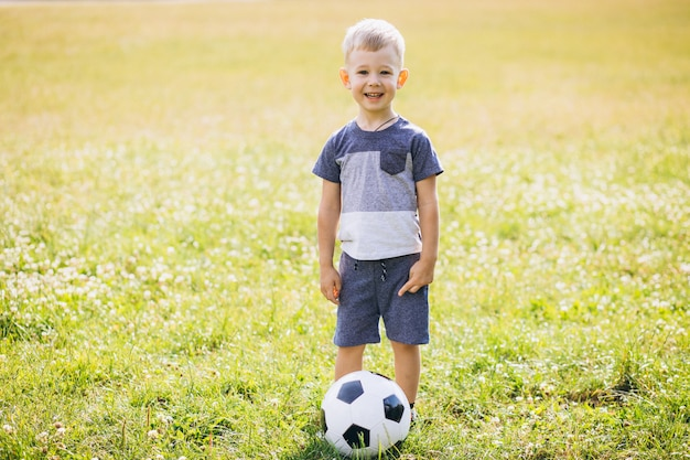 Маленький мальчик играет в футбол на поле