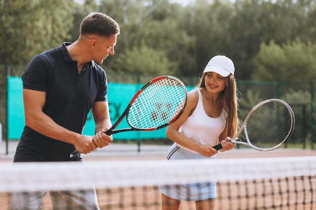 コートでテニスをしている若いカップル