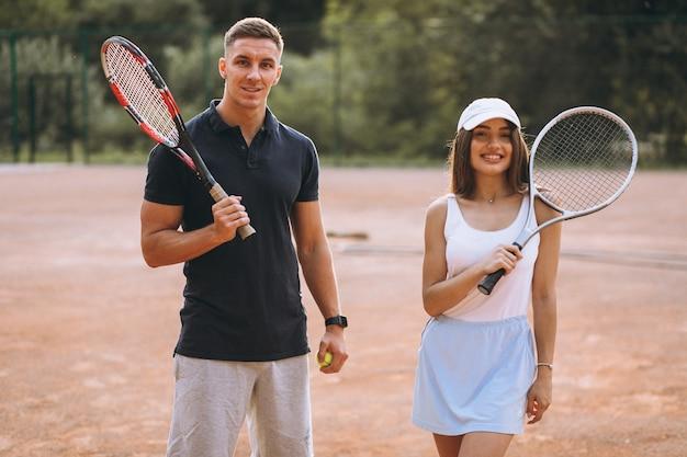 Молодая пара играет в теннис на корте