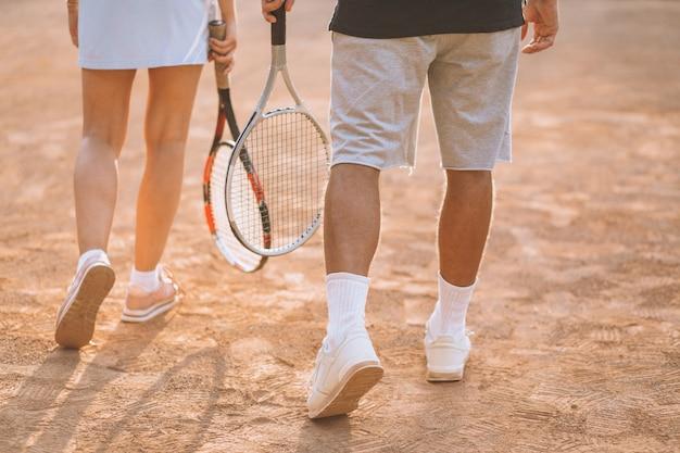 若いカップルがコートでテニスをして、足をクローズアップ
