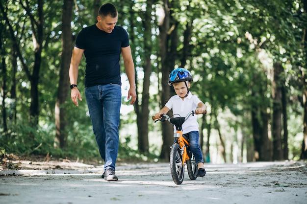 父は幼い息子に自転車に乗ることを教えています