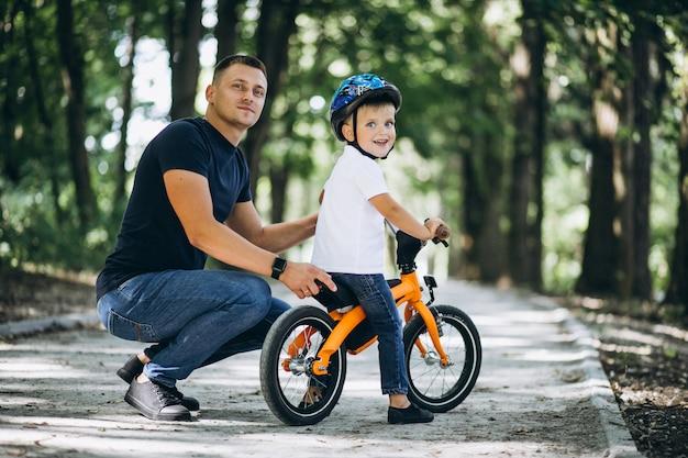 Отец учит своего маленького сына кататься на велосипеде