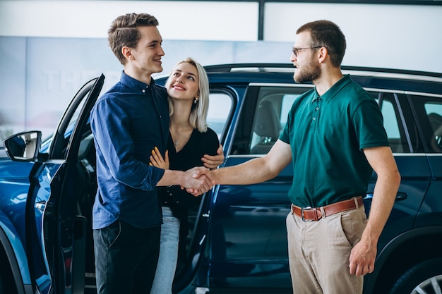 若い家族が車のショールームで車を買う