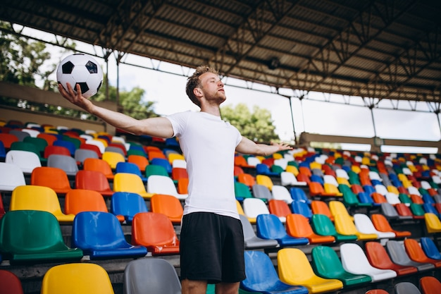 Юный футболист на трибунах наблюдает за игрой