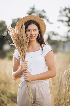 Молодая девушка в шляпе в поле пшеницы