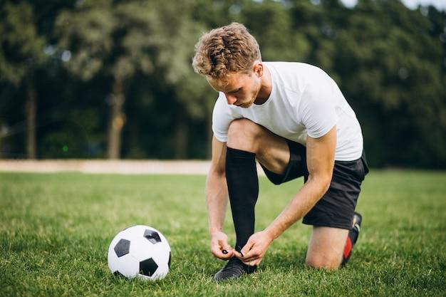 フットボール競技場で若いフットボール選手